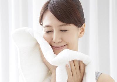 タオルで顔を拭く一般女性