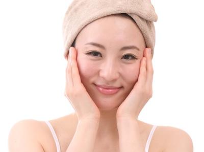 頭にタオルを巻き化粧水を浸透させる一般女性