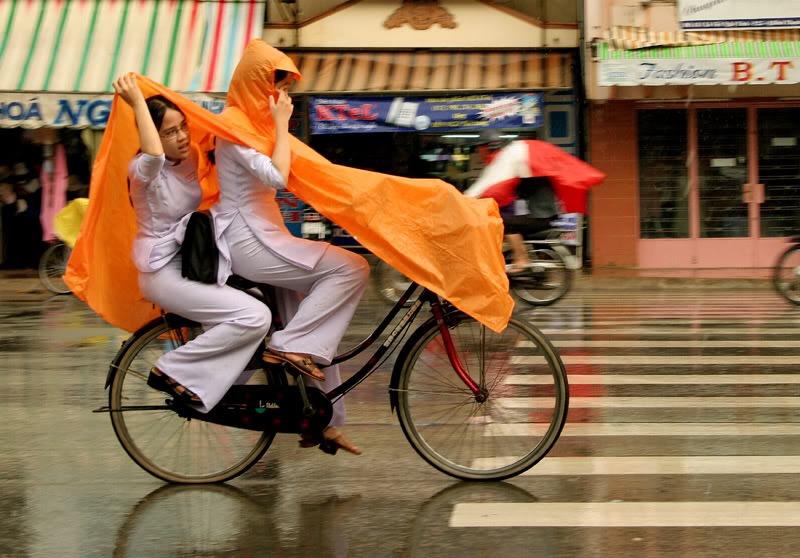白いアオザイを着て自転車に乗るベトナムの女の子