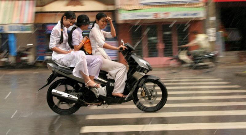 白いアオザイを着てバイクに乗るベトナムの女の子
