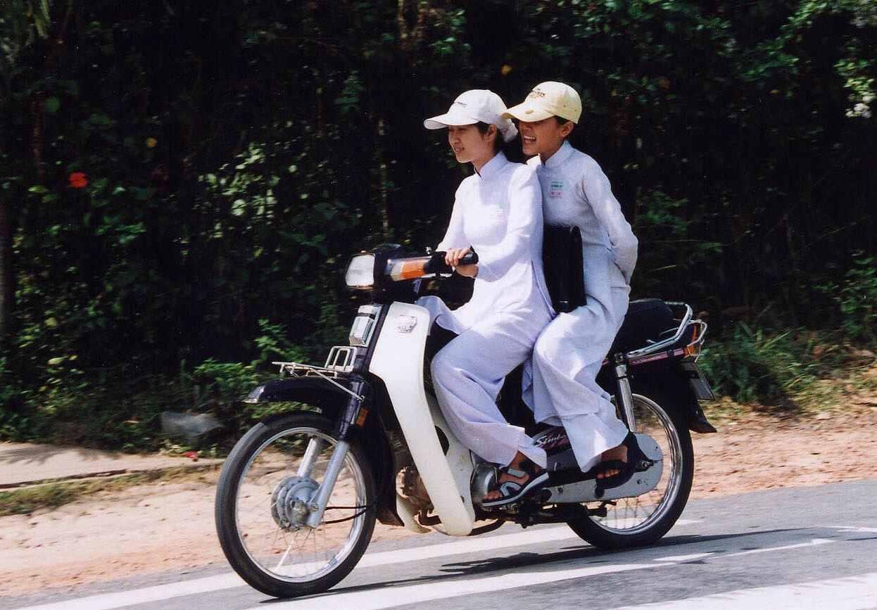 バイクに二人乗りするアオザイを着た女の子