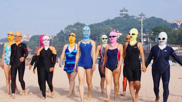 日焼け対策のため覆面マスクとウェットスーツで海で遊ぶ中国人