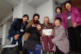 訪問先の住民の方を囲んで,神戸・広島のボランティアと交流の記念に