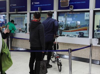 切符売り場に並ぶ自転車乗り