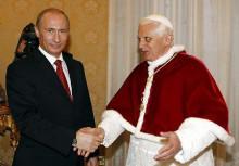 笑顔で迎えるプーチン、しかし法王の顔と左手は