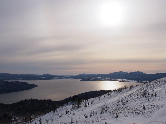 冬の屈斜路湖の上で輝く太陽