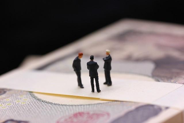 1万円札束の上に小さなビジネスマン