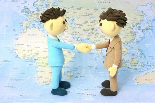 地図の上で握手するビジネスマン